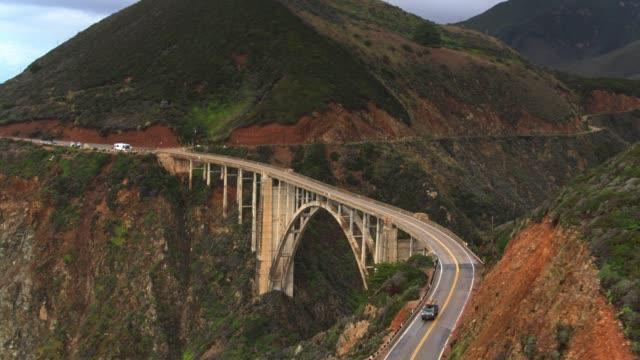 vídeos de stock e filmes b-roll de drone shot revealing bixby creek bridge - big sur