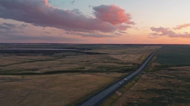 vidéos et rushes de vue de projectile de drone de route dans la campagne et le grand champ au coucher du soleil - inclinaison vers le haut