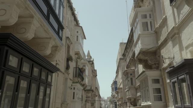 Drone smooth flying back through beautiful old street,Valletta,Malta . Old, vintage windows, balconies. - 4K