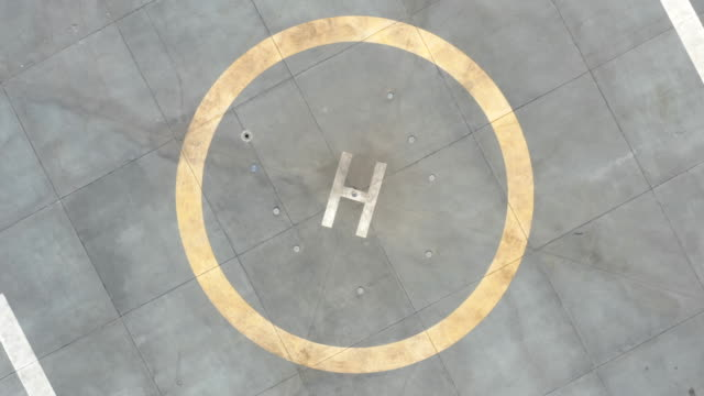 Drone Takeoff From Helicopter Helipad Drone aerial footage that depicts roof of a Hospital with helipads for helicopters. Transportation, fast delivery or emergency cases. helicopter stock videos & royalty-free footage