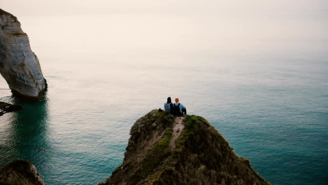 Drone tilts down over happy romantic couple watching sunset ocean view sitting on top of famous Normandy coast cliff.