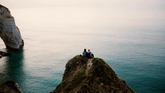 vídeos y material grabado en eventos de stock de drone se inclina sobre la pareja romántica feliz viendo atardecer vista al mar sentado en la cima del famoso acantilado de la costa de normandía. - turista