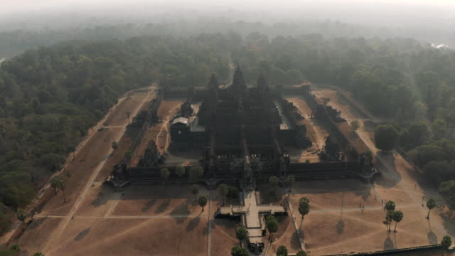 drone timelapse angkor wat temple in cambodia sunrise fog drone flight - скульптура стоковые видео и кадры b-roll