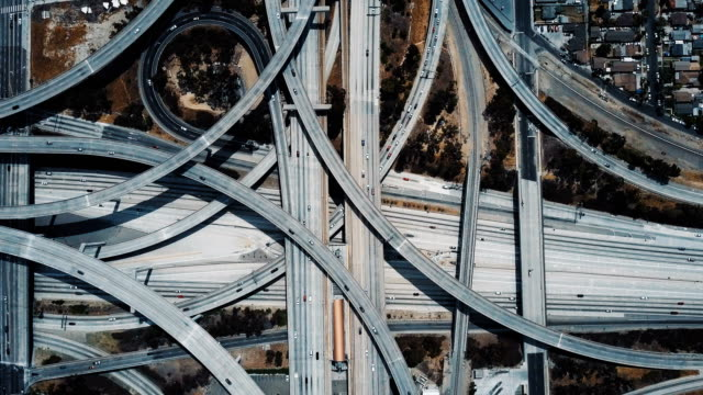 Drone top view of epic highway junction interchange with traffic moving through multiple flyovers and intersections. Abstract concept of modern transportation, architecture and engineering.