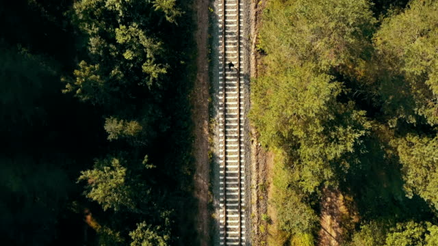 Drone top view of man running on train track. Concept of life never ending journey. Chasing dreams and surviving video