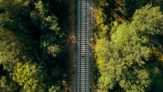Drone top view of man running on train track. Escaping from past problems. Chasing dreams and surviving life trials video