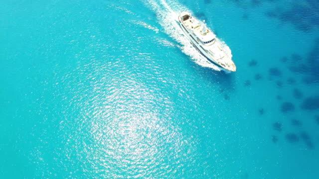 drone video of a white ship travelling across the turquoise ocean - spektakularny krajobraz filmów i materiałów b-roll