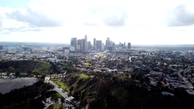 4k drone video of the downtown los angeles skyline and its surrounding houses and buildings - city skylines stock videos & royalty-free footage