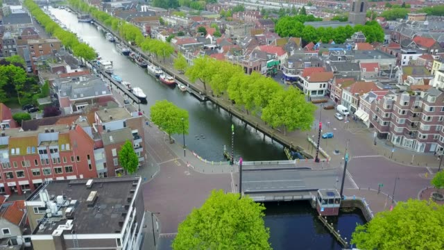 drone video of typical dutch city, village with small harbor and sailing boats and a little bridge - dutch architecture stock videos & royalty-free footage