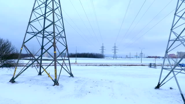 Drone view electric towers standing in a winter field. Electricity pylons Drone view electric towers in winter field. Electricity pylons and transmission lines. Aerial view high voltage power lines near highway. Electricity lines high voltage sign stock videos & royalty-free footage
