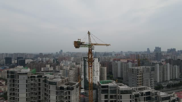 drone view move up along a building in construction and crane tower shanghai - osiedle mieszkaniowe filmów i materiałów b-roll