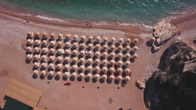 drohnenblick auf einen schönen strand mit vielen sonnenliegen und sonnenschirmen - sonnenschirm stock-videos und b-roll-filmmaterial
