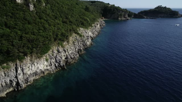 Drone view of a cliff on the Mediterranean coast by a turquoise and transparent sea Corfu Greece