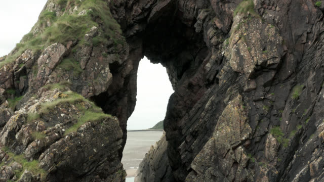 Drone view of a natural rock arch 4K drone footage of a natural arch on a Scottish coast in Dumfries and Galloway rock formations stock videos & royalty-free footage