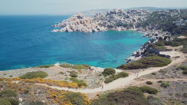 drone view of a rocky valley. amazing view of 'capo testa', emerald coast, sardinia, italy. - sardegna video stock e b–roll