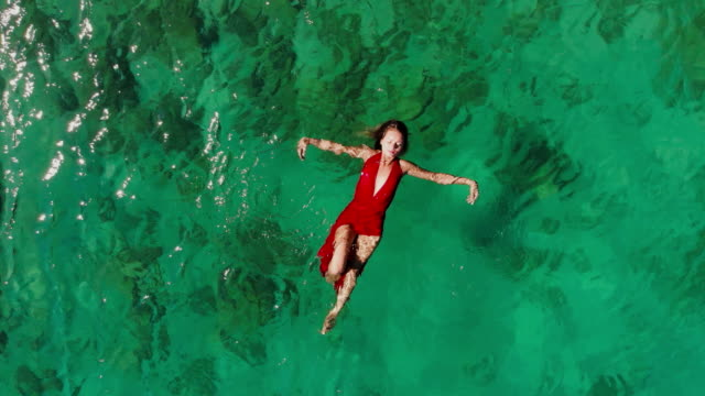 Drone View of a Woman Floating and Swimming on a Tropical Sea video