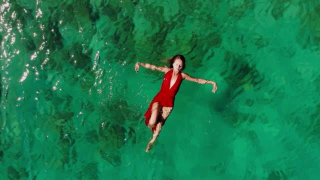 Drone vista de uma mulher boiando e nadando num mar Tropical - vídeo