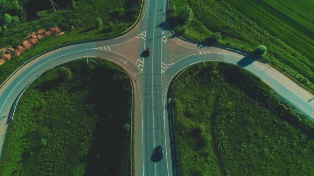 Drone view of cars traffic on highway fork junctions. 4K. Aerial view of cars driving on freeway intersection passing unbelievable landscape. Copy space. fork stock videos & royalty-free footage