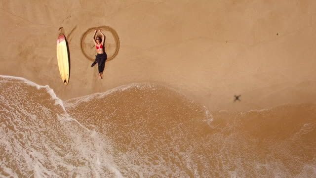 4k drone view of coastline surfer woman lying on the beach - angelo video stock e b–roll