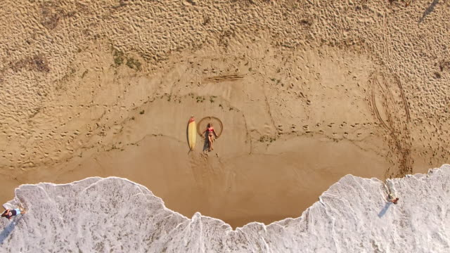 4K Drone view of coastline surfer woman on the beach
