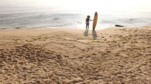 stockvideo's en b-roll-footage met 4k drone uitzicht op kustlijn surfer vrouw op het strand - afro amerikaanse etniciteit