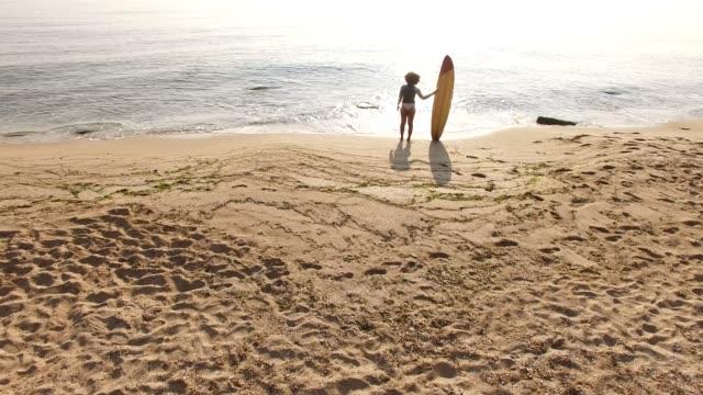vídeos de stock e filmes b-roll de 4k drone view of coastline surfer woman on the beach - afro americano