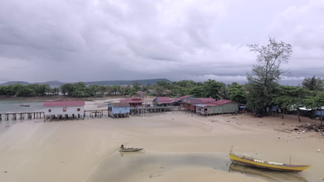 drone view of dramatic clouds over a fishing village and boats on the sand beach