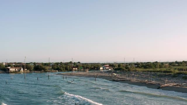güneşli bir günde balıkçı kulübelerinin drone görünümü - ravenna stok videoları ve detay görüntü çekimi
