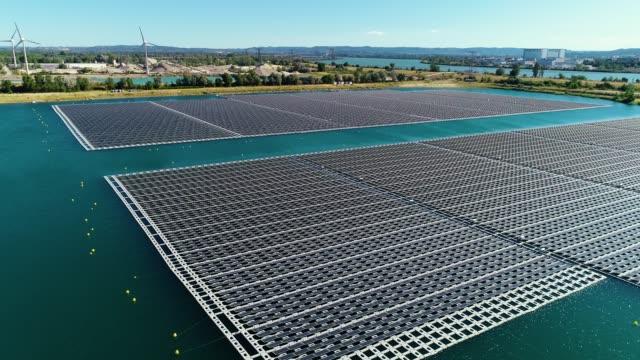 drone vy av solpaneler flyter i vatten med väderkvarnar, damm och landsbygden aera i bakgrunden, under den blå himlen. perfekt grön energi för en ren miljö - 4k - ekosystem bildbanksvideor och videomaterial från bakom kulisserna