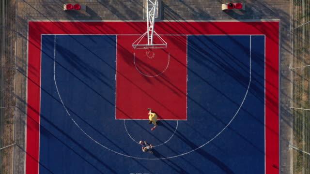 バスケットボールコート上の2人のバスケットボール選手のドローンビュー - デイフェンス点の映像素材/bロール