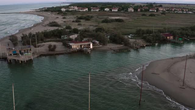 gün batımında tipik balıkçı kulübelerinin drone görünümü - ravenna stok videoları ve detay görüntü çekimi