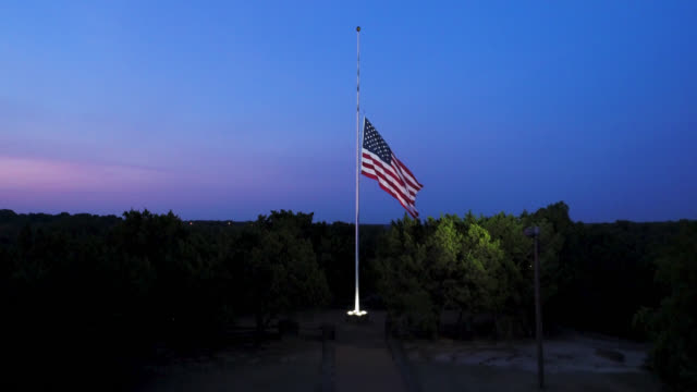 vídeos de stock e filmes b-roll de drone view of us flag at half-staff at dawn, lit by spotlight,, moving forward and up - bandeira
