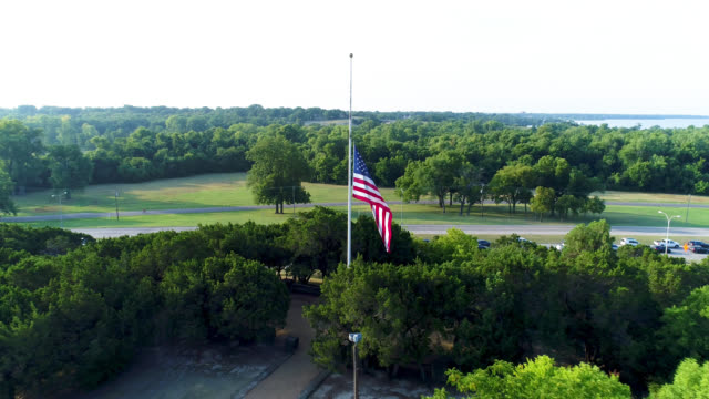 Drone view of US flag at half-staff, moving back and up Drone 4k aerial view of US flag at half-staff, flying counterclockwise in a circle around flag back to back stock videos & royalty-free footage