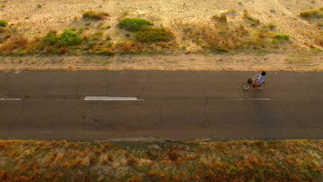 4K Drone view of Woman cycling on sunny road video