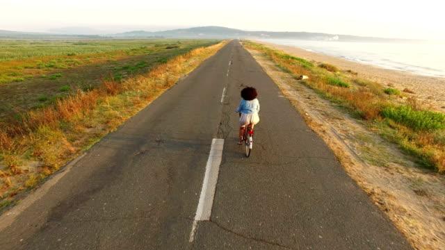 vídeos de stock e filmes b-roll de 4k drone view of woman cycling on sunny road - afro