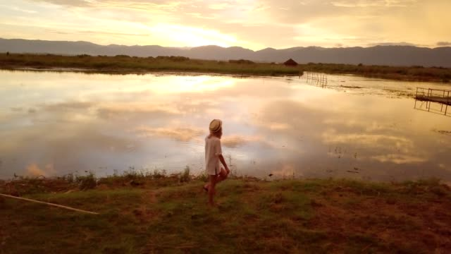 Drone view of young woman contemplating sunset from lakeshore, Myanmar Aerial view 4K Drone view of young woman contemplating sunset from lakeshore, Myanmar Aerial view, drone shot of caucasian female walking by the lake, beautiful reflection on water surface, travel people concept. 4K resolution myanmar stock videos & royalty-free footage