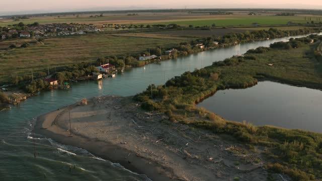 ravenna yakınlarında gün batımında nehrin denize döküldüğü drone görünümü - ravenna stok videoları ve detay görüntü çekimi
