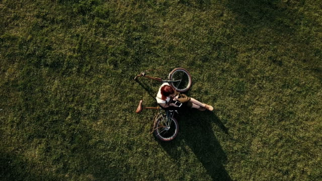 drone view woman cyclist lying on green grass and using mobile phone - ragazza auricolari rossi video stock e b–roll