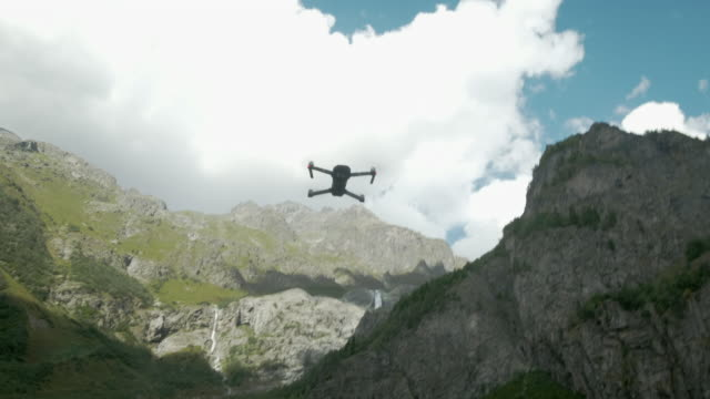 drone with rotating propellers hanging in the air on a background of lake and mountains. drone with a camera hovers in the air. close-up of an aircraft and blades that rotate - quadcopter filmów i materiałów b-roll