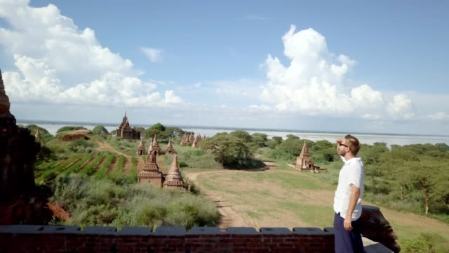 4K drone young man contemplating ancient temples Aerial view drone shot of Caucasian young man contemplating the Bagan archeological zone at sunrise, Burma  People travel discovery adventure concept Asia. Shot in 4K bagan stock videos & royalty-free footage