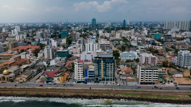Drone zooming out above Colombo, Sri Lanka panorama. Aerial view of Asian resort town, modern buildings and ocean waves Drone zooming out above Colombo, Sri Lanka panorama. Aerial view of Asian resort town, modern buildings and ocean waves. Beautiful scenery of architecture, busy street near shore and cloudy skyline. colombo stock videos & royalty-free footage
