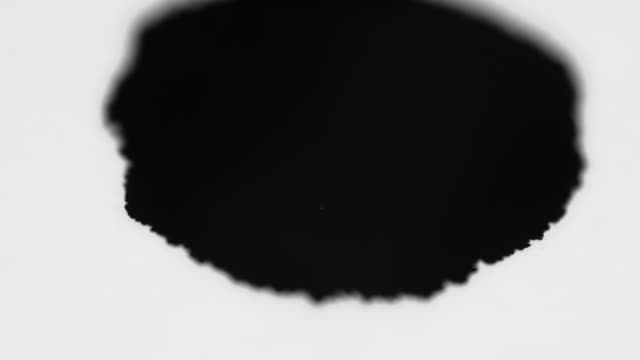 Drop of black ink falling and hitting paper video