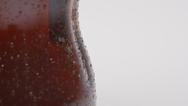 SLOW MOTION: Drop rolls down down over a curve of bottle video