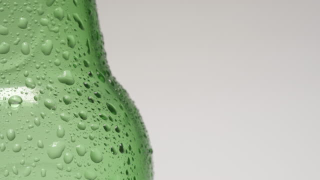 SLOW MOTION: Drop rolls down over a neck of cold green bottle video