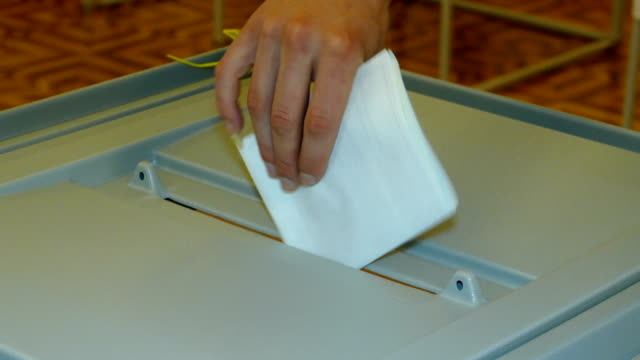 dropping an elected ballot into the ballot box for voting - vote filmów i materiałów b-roll