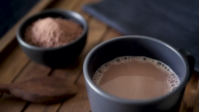 Dropping mini marshmallows into a mug of hot chocolate. Dark wood background. Slow motion 50%.