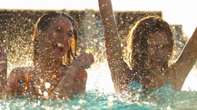 Drops falling on two women in a pool, Ultra Slow Motion Drops falling on two women in a pool, Ultra Slow Motion pool party stock videos & royalty-free footage