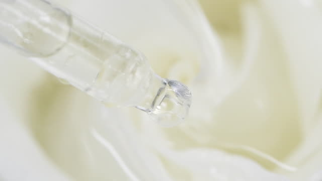 Drops from pipette falling down in water with a rose video
