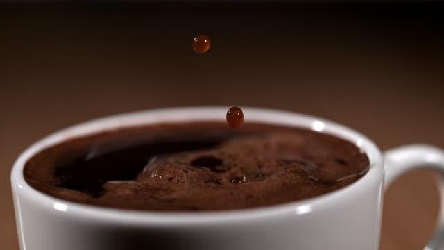 slo mo drops of a coffee falling into a cup - coffee стоковые видео и кадры b-roll