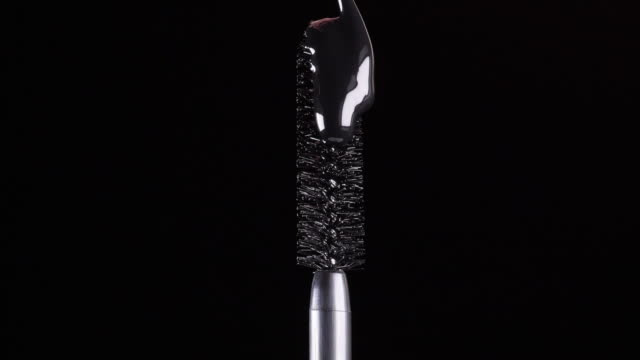 drops of black mascara fall on the brush on a black background 1 - video